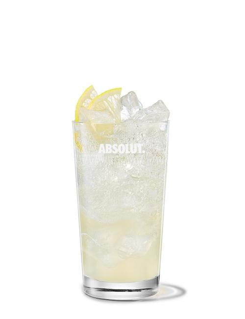 peach vodka collins against white background